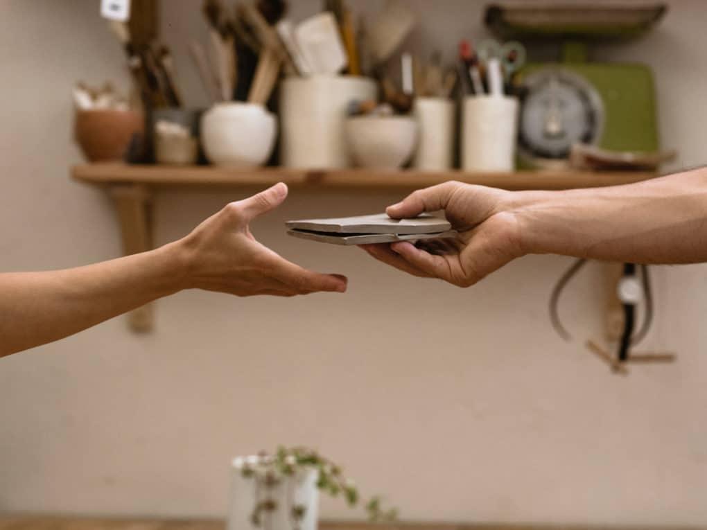 Dois braços, entregando um produto para o outro