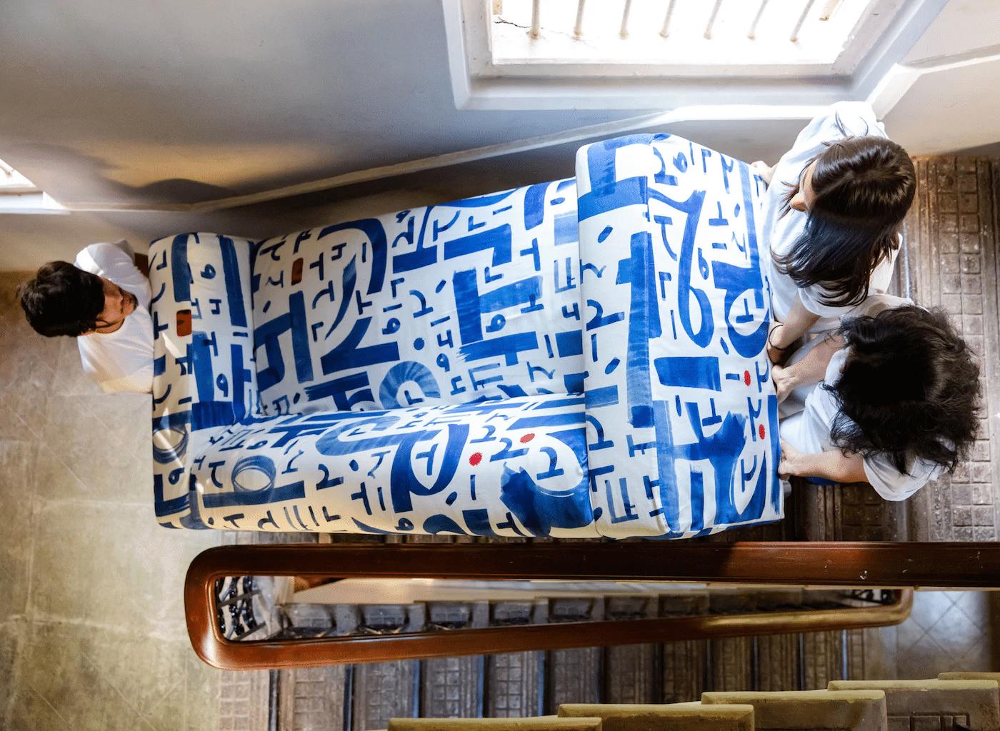 três pessoas subindo com um colchão pela escada